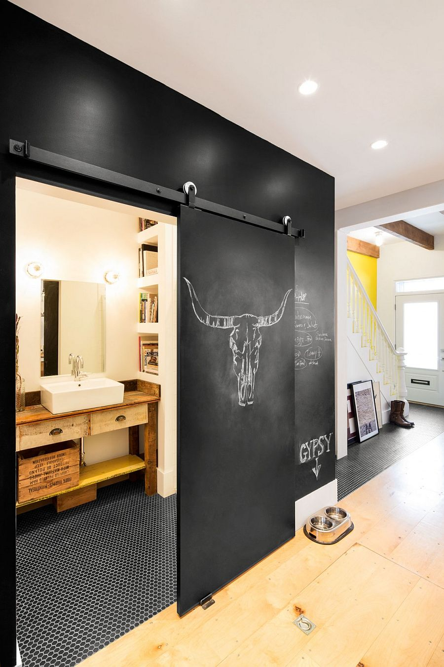 Chalkboard wall and sliding door hide the tiny bathroom on lower level