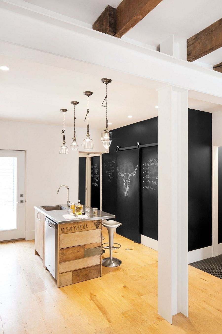 Chalkboard wall in the kitchen along with a tiny island clad in reclaimed wood