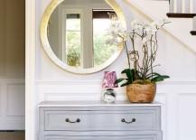 Clean-and-elegant-decor-with-sparkling-round-mirror-and-dresser-near-stairway-217x155