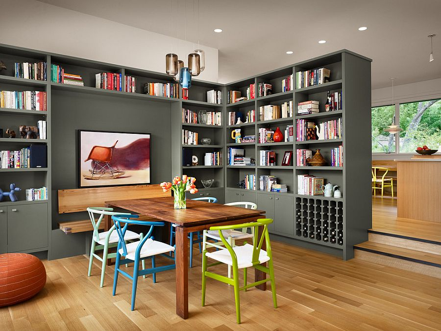 Colorful collection of wishbone chairs and gorgeous gray bookshelves add to the charm of this dining room