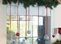 Colorful glittery ornaments hung with ribbon from garland above window