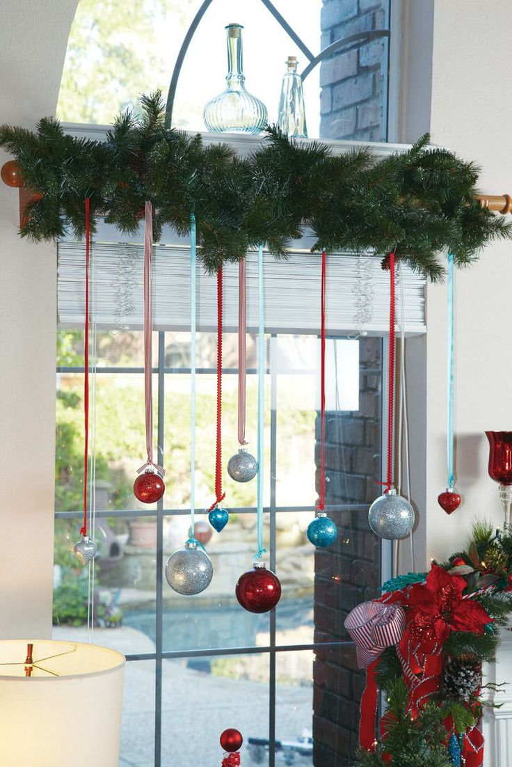 view in gallery colorful glittery ornaments hung with ribbon from garland above window