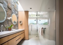 Contemporary bathroom combines glass tile with the classic stone wall