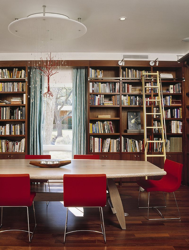 Custom chandelier and fabulous red chairs add color to the home library / dining room [Design: McKinney York Architects]
