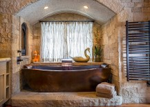 Custom copper bathtub and stone backdrop steal the show here