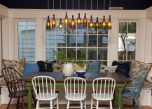 DIY wine bottle lighting above the cozy dining space