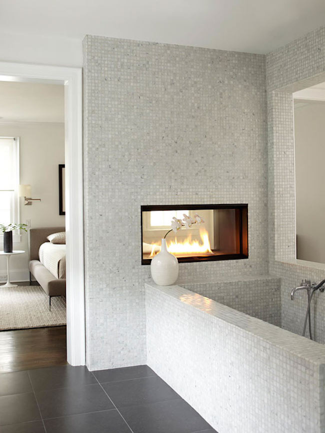 Dual fireplace in a marble tiled bathroom