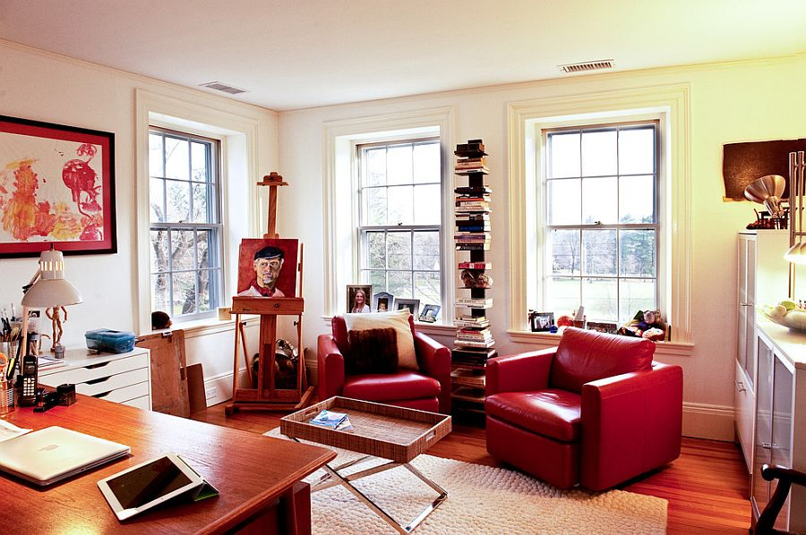 Eclectic home office uses plush leather chairs to bring in a dash of red