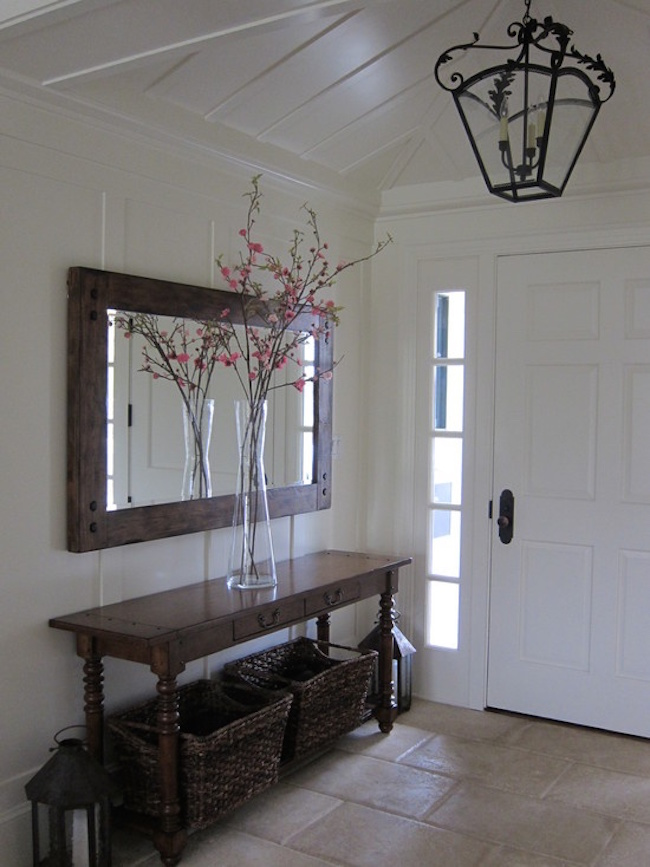 Entryway with a long dark table and matching mirror