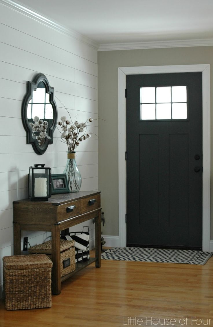 Entryway with a small irregular mirror hung above table