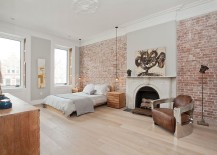 Exposed brick walls and classic fireplace inside the Scandinavian bedroom [Design: Jensen C. Vasil Architect]