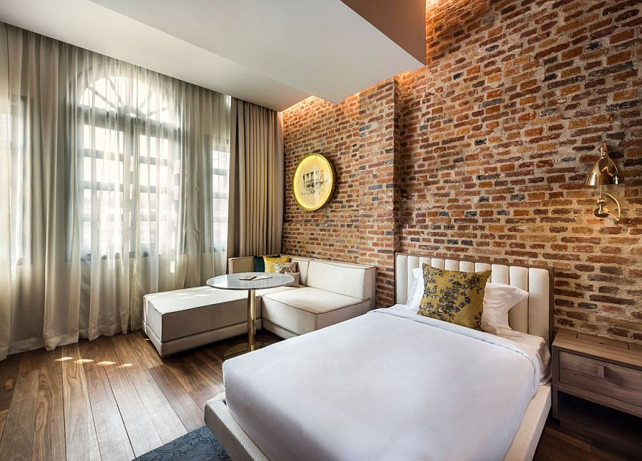 Exposed brick walls bring historic context to the refined, modern interiors of Loke Thyee Kee Residences