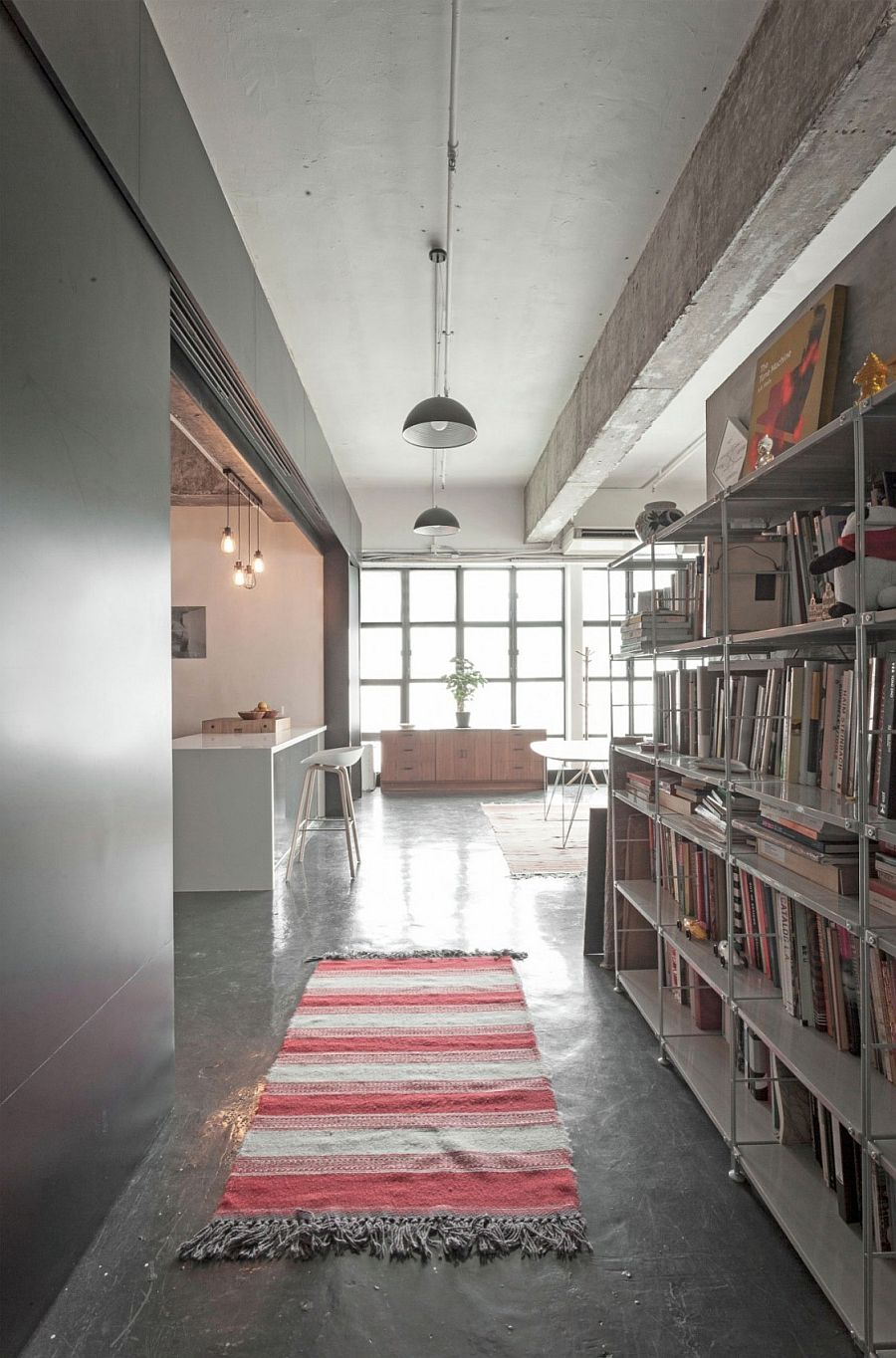 Exposed concrete surfaces and gray walls give the room an industrial vibe