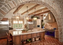 Exquisite kitchen with stone walls and terra-cotta tile herringbone flooring