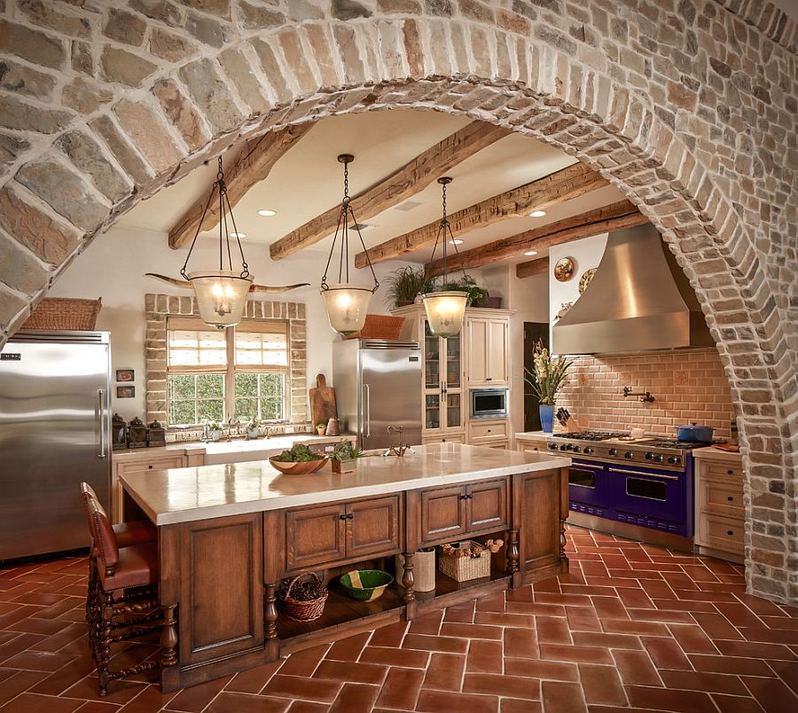 Exquisite kitchen with stone walls and terracotta tile herringbone flooring [Design: Thompson Custom Homes]