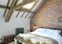 Farmhouse style bedroom with wooden ceiling beams, skylight and exposed brick wall [Design: PAD studio]