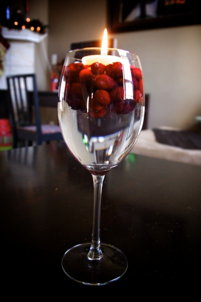 Floating candle in wine glass with water and cranberries