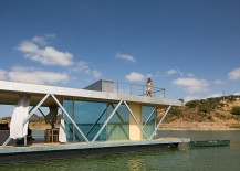 Floor-to-ceiling glazing surrounds the living area of the houseboat