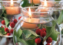 Glass bowls filled with water holly and floating candles 217x155 17 Easy DIY Holiday Candle Holders