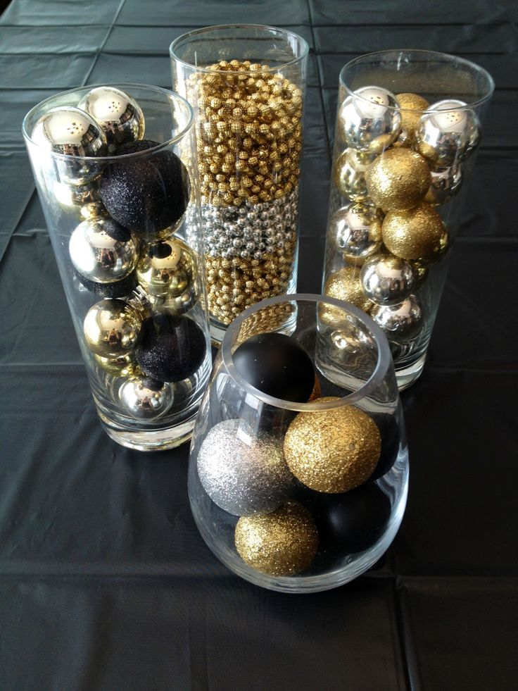 Gold, black, and silver Christmas ornaments in glass cylinders