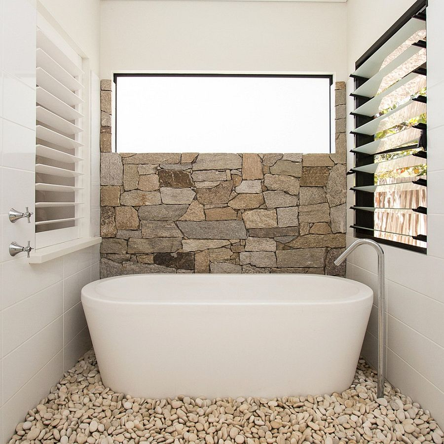 half wall in natural stone and pebbles on the floor turn the the small bathroom into
