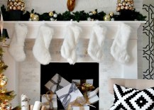 Holiday mantel with white stockings and gifts piled in fireplace