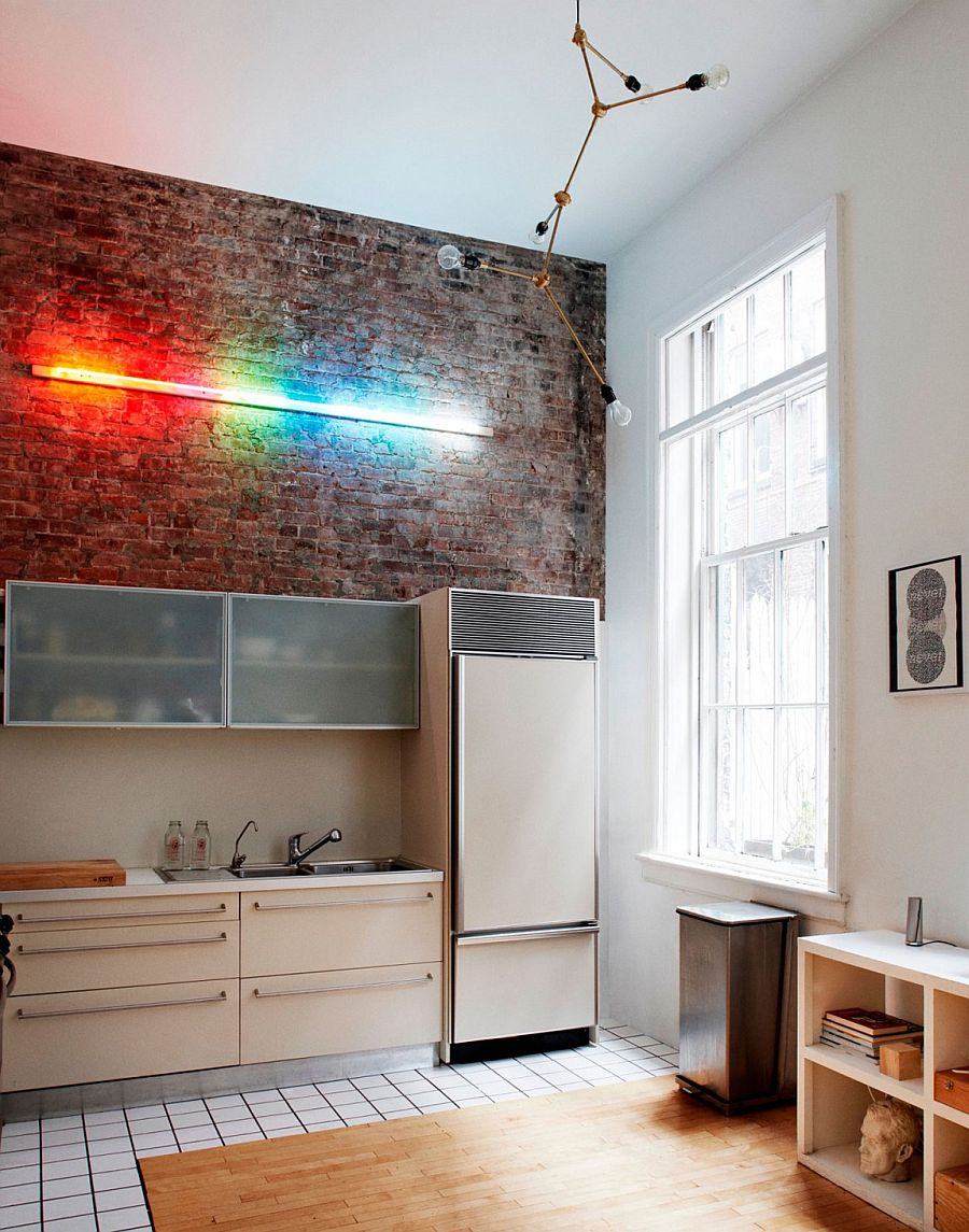 Interesting use of lighting highlights the exposed brick wall in the double height kitchen