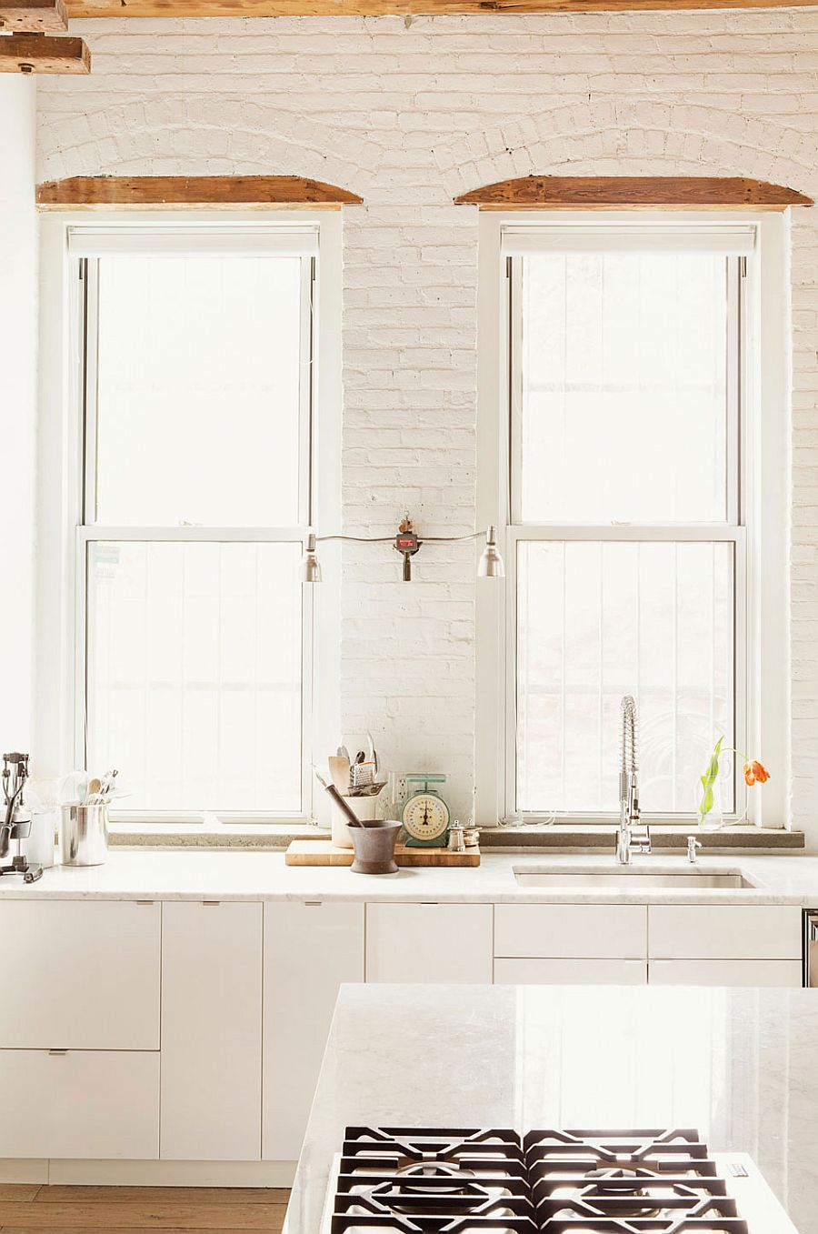 Kitchen in white with exposed brick walls and large windows