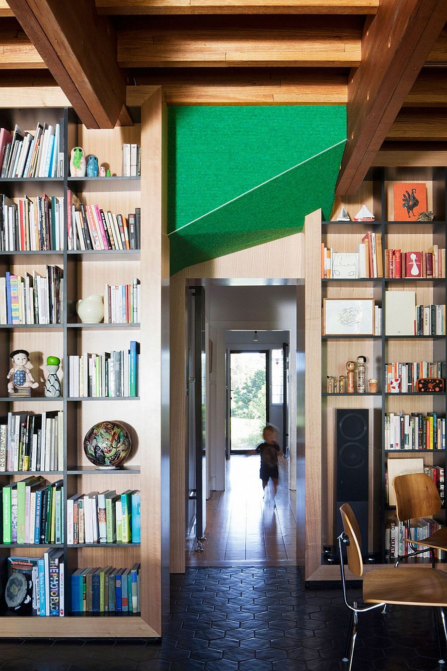 Large bookshelves and wooden walls separate spaces inside the Doll's House