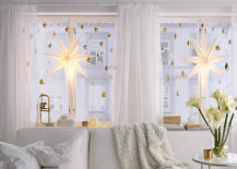 Large bright star lights hung with smaller ornaments in window