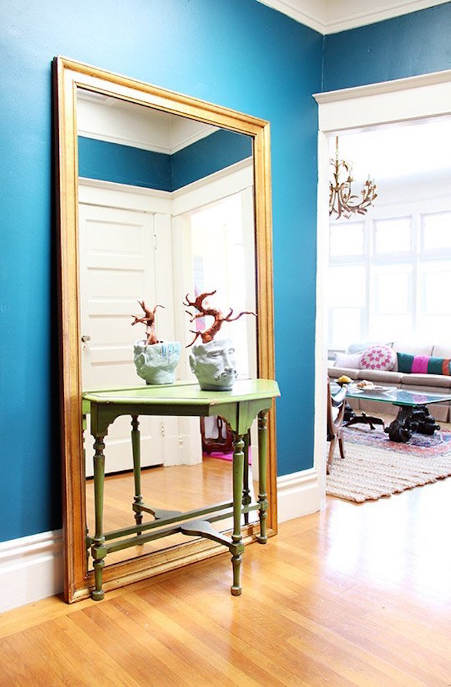 Large full-length mirror behind a small entryway table
