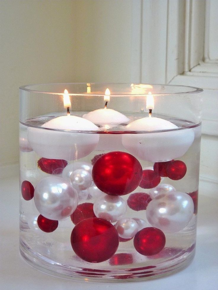 Large glass cylinder with Christmas ball ornaments and floating candles