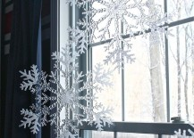 Large snowflakes hung with fishing wire in a window