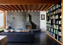 Living-area-with-dark-brick-wall-backdrop-and-large-bookshelves-217x155