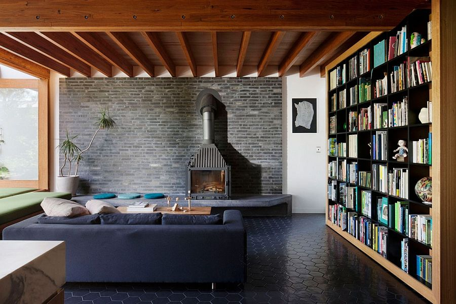 Living area with dark brick wall backdrop and large bookshelves
