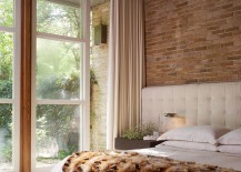 Midcentury modern bedroom employs cozy bedding and rug to contrast exposed brick wall [From: Kisabeth Furniture]