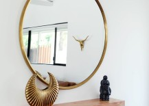 Minimal entryway decor with a large round mirror with gold frame