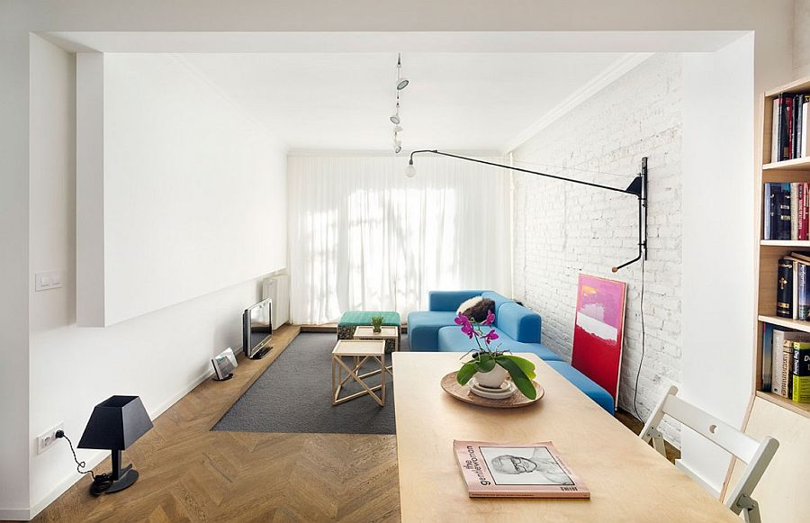 Modern eclectic living room with modular sofa, brick walls and a TV on the floor