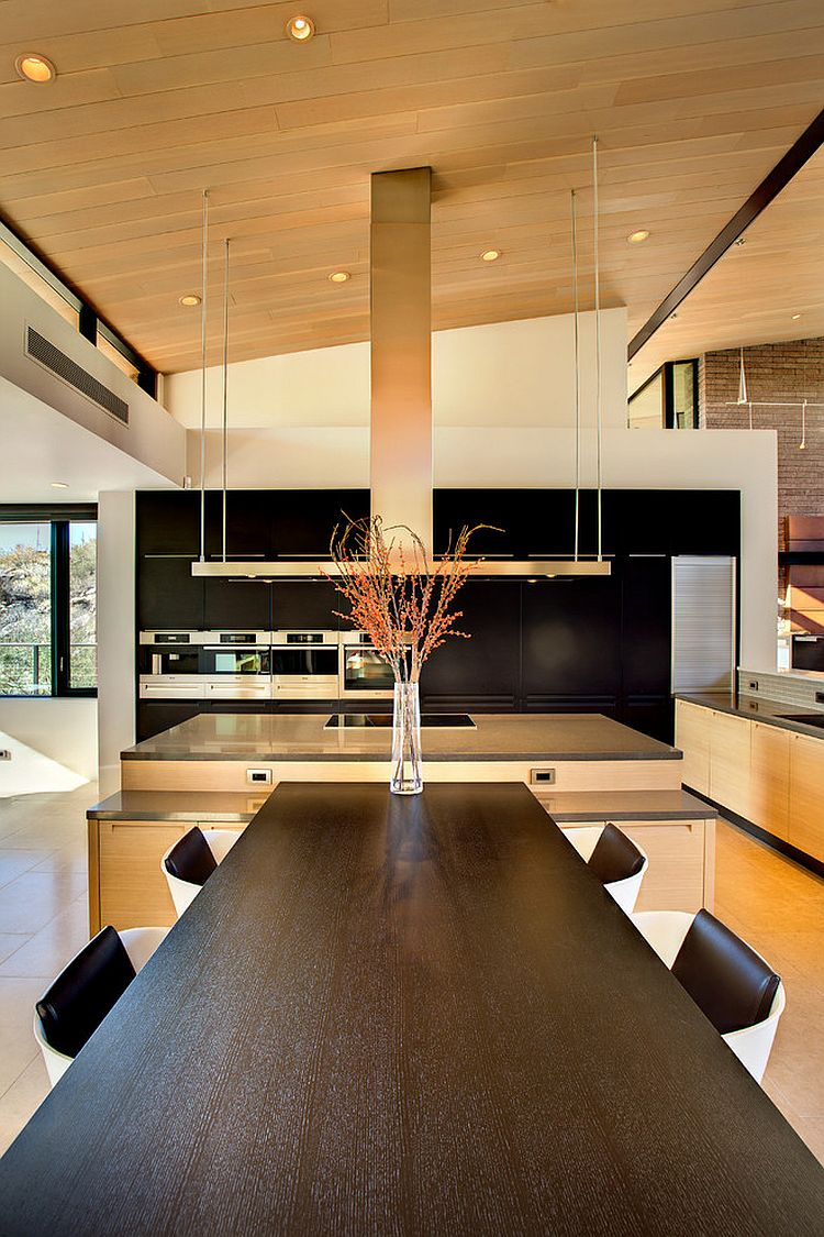 Modern kitchen and dining area with dark wall for cabinets and appliances