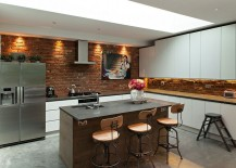 Modern kitchen with brick walls and contemporary cabinets in white