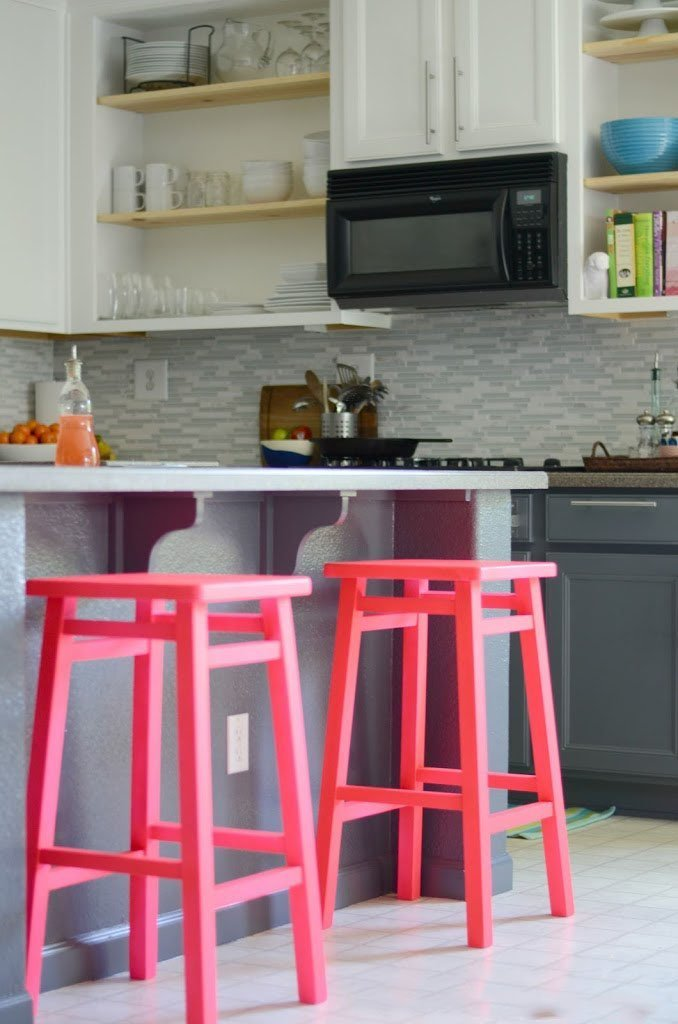Neon pink bar stools bring some color to this kitchen