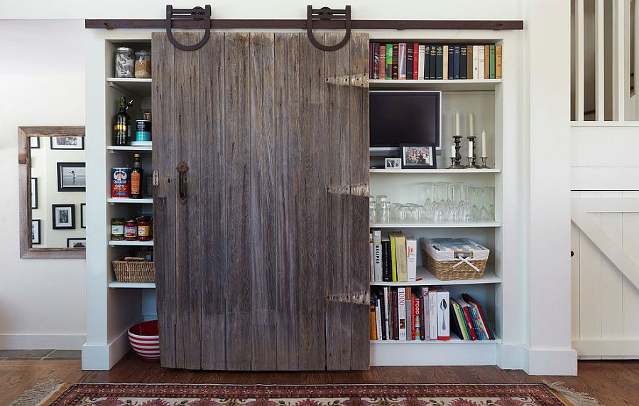 Old, reclaimed sliding barn door for the kitchen cabinet and pantry [From: Nat Rea Photography]