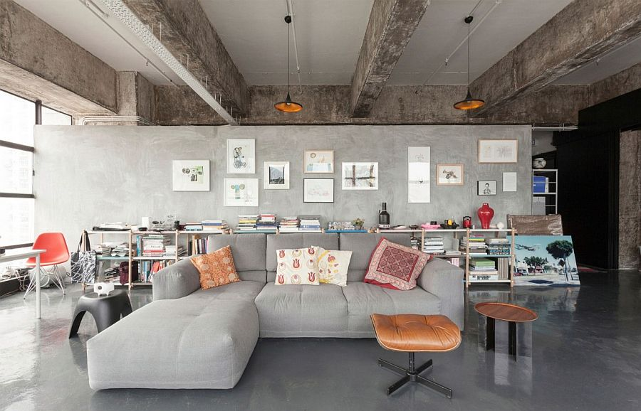 Open plan living area of industrial loft with plish gray couch