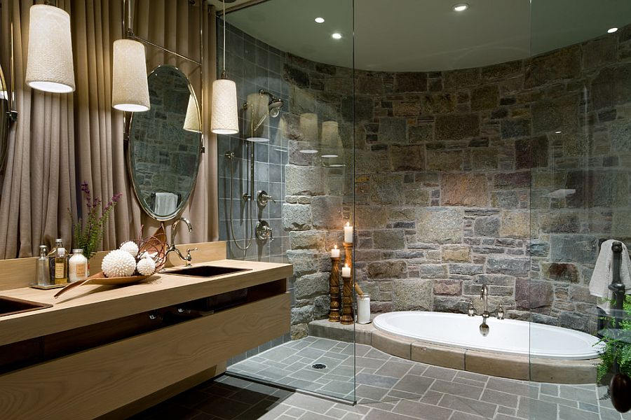 Opulent bathroom with a sunken Jacuzzi and a curved stone wall [Design: Lisa Stevens & Company]