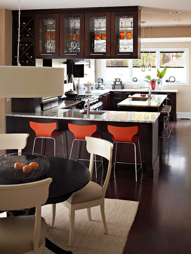 Orange bar stools in a dark wood kitchen
