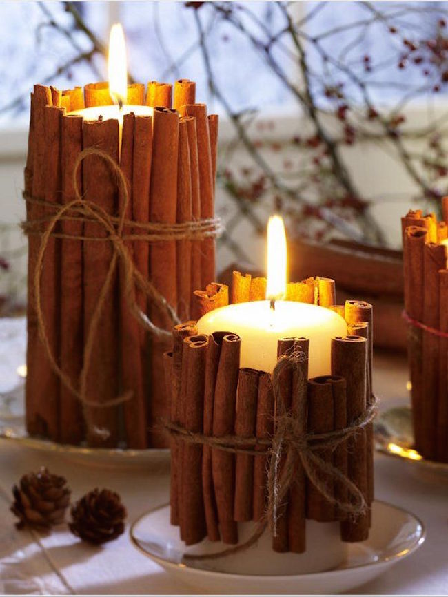 Pillar candles wrapped in cinnamon sticks
