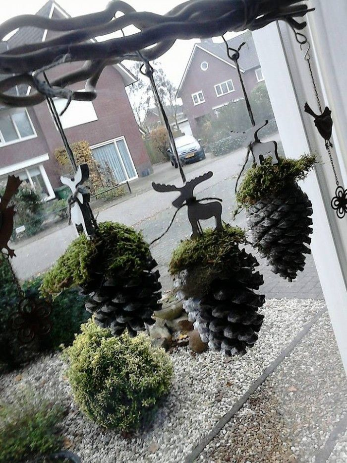 Pinecones with moss and reindeer figurines hung in window