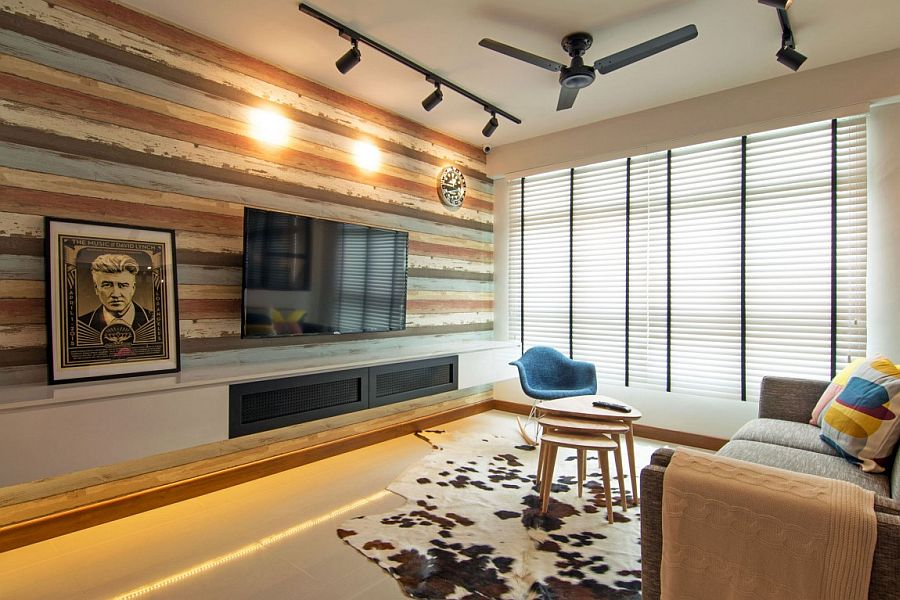 Recliamed wooden wall and unassuming decor give the living space a cozy, contemporary ambiance