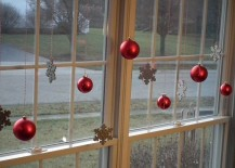 Red glass balls and snowflake ornaments hung in windows