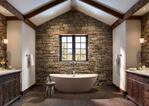Rough cut stone wall and wooden ceiling beams create a cozy ambiance in the bathroom